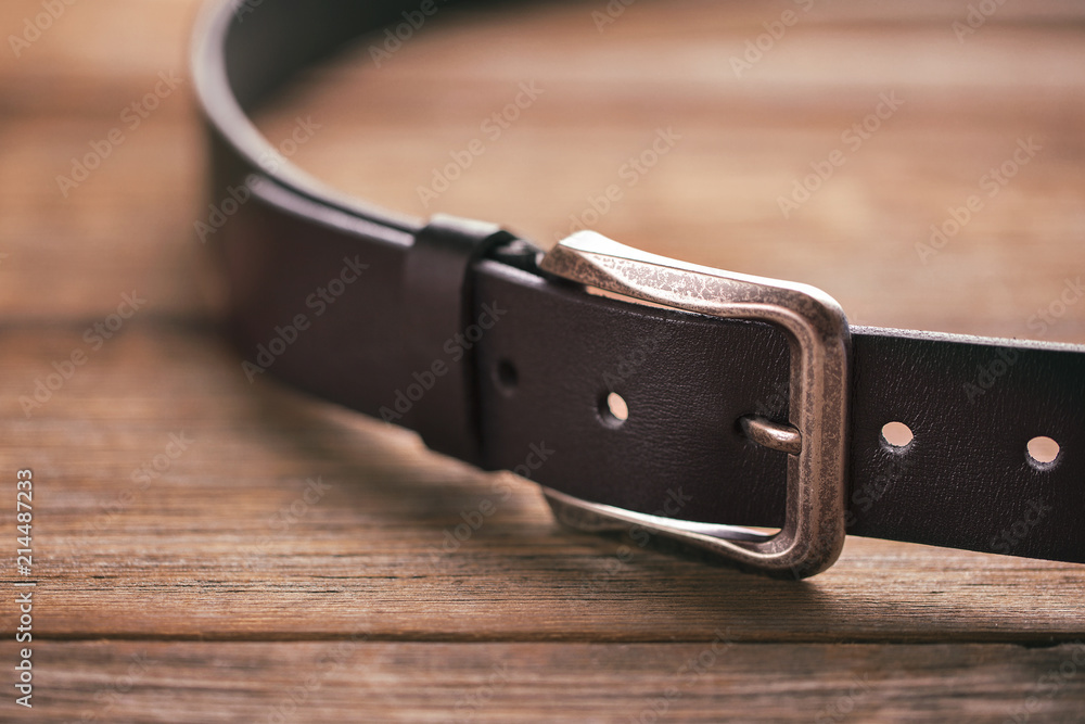 Fototapeta Leather belt on a wooden table