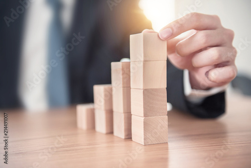Foto Close up Businessman hand arranging wood cube stacking as step stair