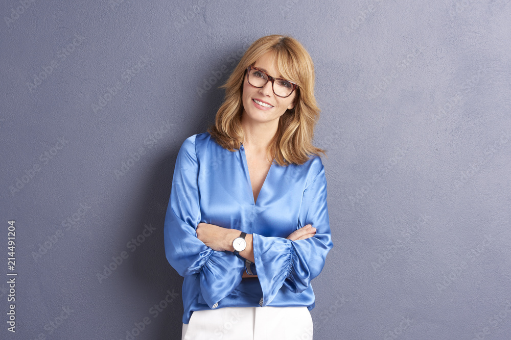 Fototapeta Confident female portrait. Portrait of an attractive middle aged woman posing against a grey background in the studio.