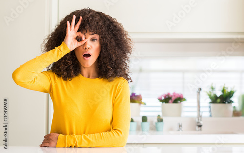 African American Woman Wearing Yellow Sweater At Kitchen Doing Ok