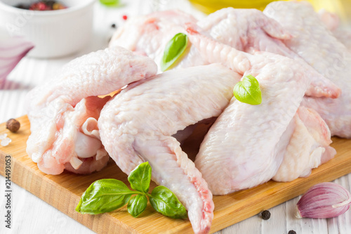 Raw chicken wings on a cutting board. Ingredients for cooking, spices, onion and garlic
