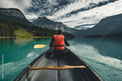 Leinwand Poster Young Man Canoeing on Emerald Lake in the rocky mountains canada with canoe and life vest with mountains in the background blue water