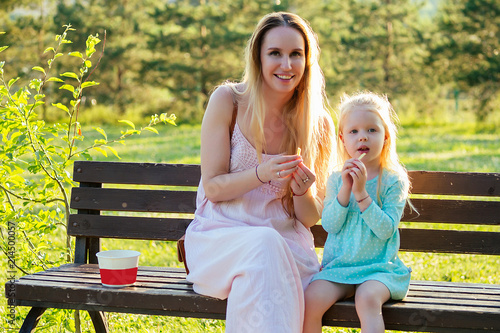 cute little blonde girl daughter eating french fries together with a beautiful mother in the park