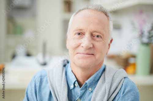Obraz Mature grey-haired man in denim shirt looking at you while sitting in the kitchen - fototapety do salonu