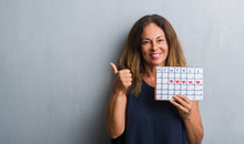 Middle Age Hispanic Woman Standing Over Grey Grunge Wall Holding Period Calendar Pointing And Showing With Thumb Up To The Side With Happy Face Smiling