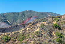 Southwest Mountains After Forest Fire With Burned Hills And Red Fire Retardant Covering Hillsides To Stop The Spread Of Fire