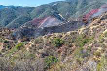 Mountains In Southwest Burned From Forest Fire With Fire Retardant Covering Hillsides On Summer Morning