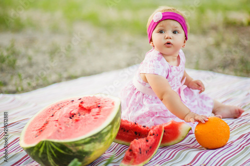 Foto  Baby girl on picnic. eating watermelon outdoors. Childhood.