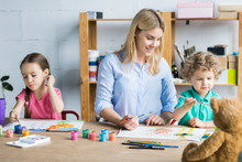 Young Woman Crafting Together With Her Children Sitting At Wooden Drawing Table