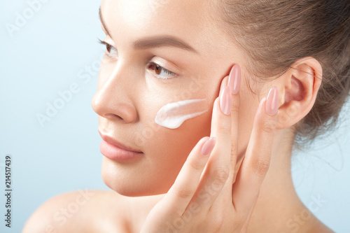Stampa su Tela Young beautiful woman applies cream on clean perfect skin