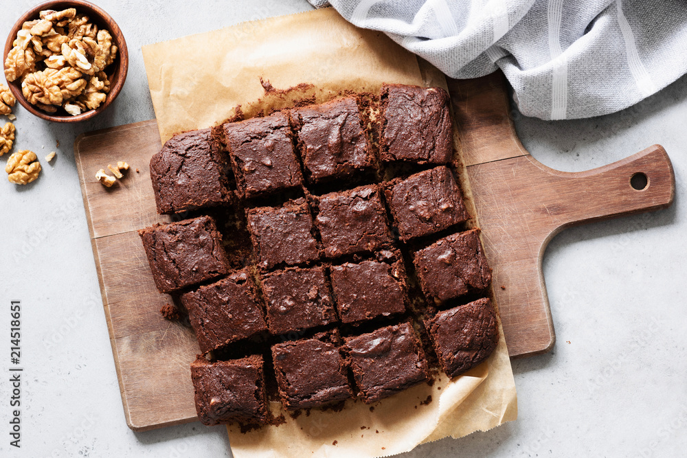Chocolate brownie squares with walnuts on cutting board, top view, horizontal composition. Flat lay food