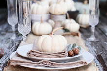 Place Setting On A Rustic Farmhouse Country Table With Mini White Pumpkins, And Crystal Glasses For Thanksgiving Day Or Halloween.