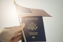 Holding Passport Of USA And American Flag In Left Hand, White Background. Light Flare Effect