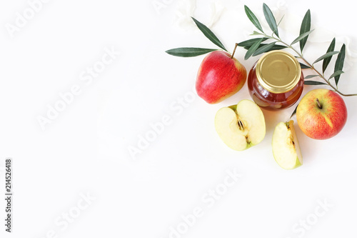 Rosh hashana, Jewish New Year greeting card, invitation. Food styled stock composition with honey jar, apples, olive branch and ribbon isolated on white table background. Flat lay, top view.