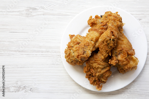 Fototapeta Fried chicken legs on a white round plate with copy space, top view. From above, overhead, flat lay. obraz