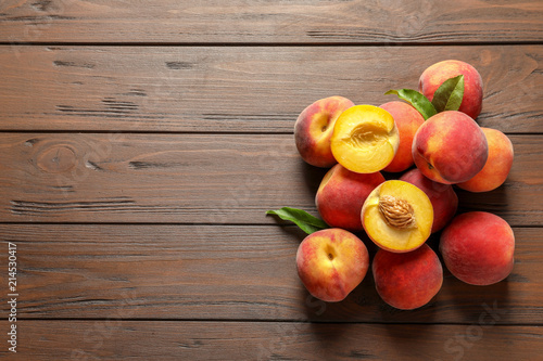 Fresh sweet peaches on wooden table, top view