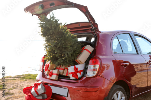 fototapeta na ścianę Red car with gift boxes and Christmas tree on beach. Santa Claus delivery
