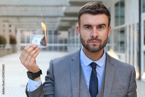 Fotografía  Serious businessman burning dollar bill