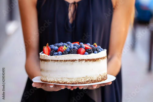 The girl is holding a cake with forest berries, strawberries, blueberries, on the street in the city Fototapeta
