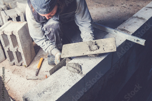 Real construction worker bricklaying the wall using tools.