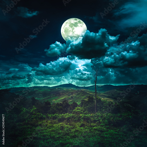 Beautiful night sky with cloudy and full moon above mountain range.