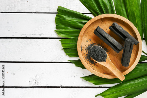 Photo Bamboo charcoal and powder on wooden table. copy space