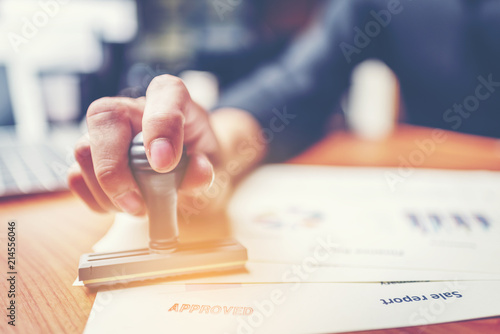 Close-up hand stamping of businessman for signing approval on documents , busine Canvas Print