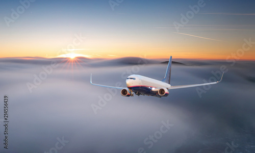 Foto op Aluminium Vliegtuig Passenger airplane. Landscape with big white airplane is flying in the red sky over the clouds and sea at colorful sunset. Passenger aircraft is landing at dusk. Business trip. Commercial plane.