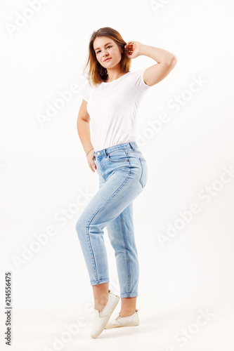 e0a3df96c8a Beautiful girl teenager in white t-shirt and jeans poses in white studio