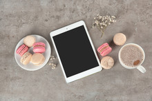 Flat Lay Composition With Tasty Macarons, Cup Of Coffee And Tablet Computer On Grey Background