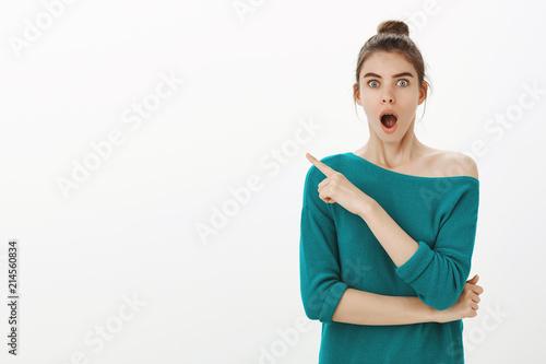 Studio shot of impressed happy joyful girl with bun hairstyle in stylish loose s Billede på lærred