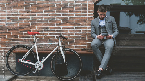 Photo  Handsome young adult man wearing suit checking phone near his classic bicycle in