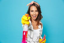 Photo Of Brunette Woman 20s Spraying Detergent And Holding Sponge While Cleaning In Yellow Rubber Gloves For Hands Protection, Isolated Over Blue Background