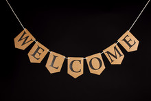Welcome Home Banner. Greeting With The Word Welcome Written In Letters Hanging On A Bunting String. Isolated Against Black Background.