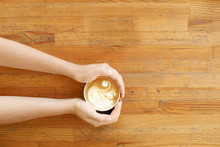 Top View Of Young Woman Hands Holding Black Cup Of Coffee With Swan Shape Foam Latte Art. Female Drinking Cappuccino, Sitting By Grunged Scratched Wooden Bar Table. Background, Close Up, Copy Space.