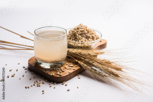 Foto Barley water in glass with raw and cooked pearl barley wheat/seeds