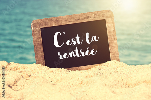 Papiers peints Nature C'est la rentrée (meaning Back to school in French) written on a vintage chalkboard in the sand of a beach