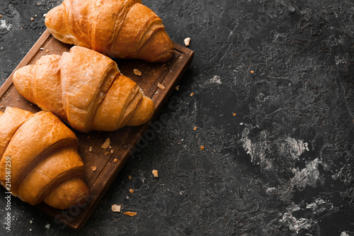 Fototapeta  Board with tasty croissants on grey textured background