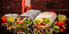 Two Burrito, Black And White Lavash With Chicken, Mushrooms, Salad, Cherry Tomatoes, Lime, And Salsa. Copy Space, Selective Focus