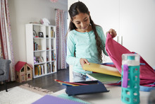 Young Girl In Bedroom Packing Bag Ready For School