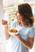 Cheerful Young Woman Eating Healthy Breakfast