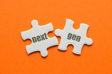 Two White Details Of Puzzle With Text Next Gen On Orange Background, Close Up