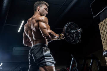 Fototapeta na wymiar A young brutal male athlete is a bodybuilder with a perfect abs, exercising in the gym. Concept - strength, bodybuilding, styrodes, weightlifting, diet, muscles, sports nutrition, personal trainer