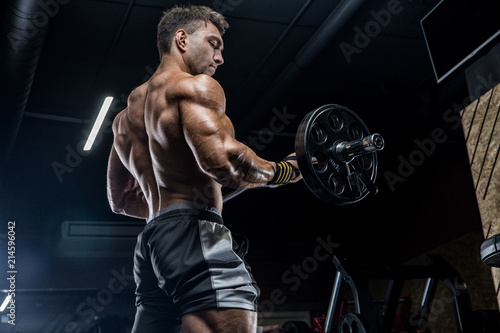 Poster Fitness A young brutal male athlete is a bodybuilder with a perfect abs, exercising in the gym. Concept - strength, bodybuilding, styrodes, weightlifting, diet, muscles, sports nutrition, personal trainer