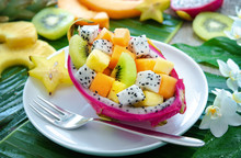 Exotic Fruit Salad Served In Half A Dragon Fruit On Palm Leaves
