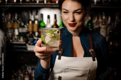Poster de jardin Bar Bartender girl holding an fresh cocktail with lime and mint