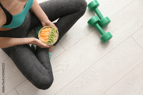 Young woman with bowl of tasty oatmeal after training indoors