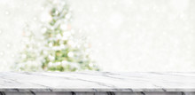 White Marble Table Top At Blur Bokeh Christmas Tree Decor With String Light Background When Show Falling,Winter Holiday Greeting Card.