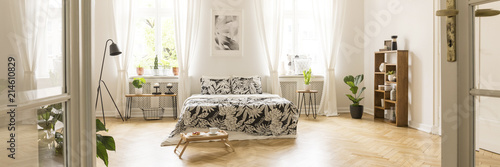Obraz Glass door entrance into a beautiful, bright bedroom interior with breakfast tray on a wooden floor and black floral pattern sheets on a comfy bed - fototapety do salonu