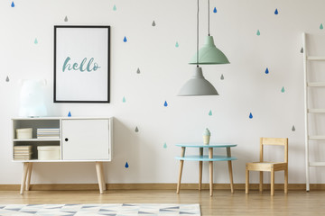 Real photo of a pastel blue and mint kid room interior with a poster above a white cupboard standing next to a round, wooden table